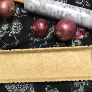 Top view of a tart crust, three red onions, and a marble rollling pin on a black tea towel